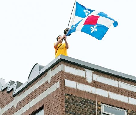 Un jeune manifestant juché sur le toit d'un immeuble, samedi dernier, à Montréal