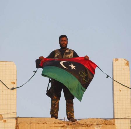 Un combattant rebelle accroche son drapeau au quartier général de Kadhafi.<br />