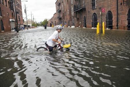 Un résidant de Brooklyn tente de circuler à vélo dans des rues inondées. New York, qui craignait le pire, a été relativement épargnée par Irene.<br />